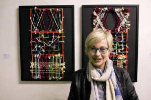 """Eva Bakalar vor ihrer Arbeit in der Ausstellung """"farbig"""""""
